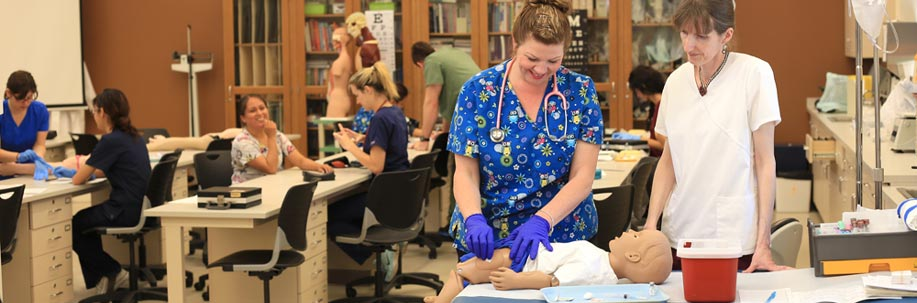 Instructor Monika Bell working with a medical assisting student in the classroom.